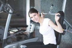 Woman weight training at gym.Exercising on pull down weight machine.Woman doing pull-ups exercising lifting dumbbells. royalty free stock photo