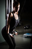 Woman weight training at gym.Exercising on pull down weight machine.Woman doing pull-ups exercising lifting dumbbells Royalty Free Stock Image