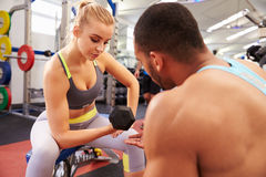 Woman weight training at a gym getting advice from a trainer Royalty Free Stock Photo