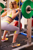 Woman weightlifting barbells at a squat rack in a gym Stock Image
