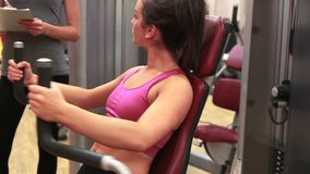 Woman on weights machine talking to trainer. In gym stock footage