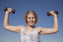 Woman weights up blue sky Stock Image