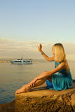 Woman welcomes boat Royalty Free Stock Photo