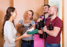 Woman welcomes joyful friends Stock Photography
