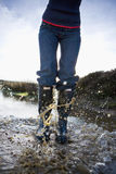Woman in wellingtons splashing in water Royalty Free Stock Image