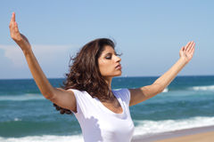 Woman wellness. Concept photo: young beautiful woman with arms open on beach Royalty Free Stock Images