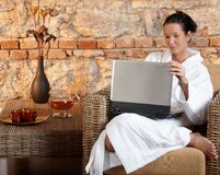 Woman in wellness environment with computer Royalty Free Stock Images