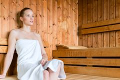 Woman in wellness spa enjoying sauna. Young woman in wellness spa relaxing in wooden sauna stock photo