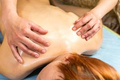 Woman in wellness spa having aroma therapy massage with essential oil,Woman enjoying a Ayurveda oil massage treatment in. A spa,Massage Techniques,back massage royalty free stock photography