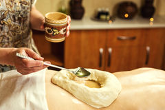 Woman in wellness spa having aroma therapy massage with essential oil,Woman enjoying a Ayurveda oil massage treatment in. A spa,Massage Techniques,back massage stock photography