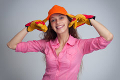 Woman wering baseball cap and construction gloves Stock Photography