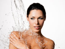 Woman with wet body and splashes of water. Beautiful naked woman with wet body and splashes of water Stock Photography