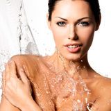 Woman with wet body and splashes of water Stock Images
