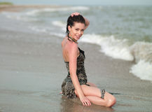 Woman in a wet dress. Pretty woman in a wet dress sitting on the beach Stock Images