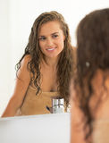Woman with wet hair in bathroom looking in mirror Stock Photography
