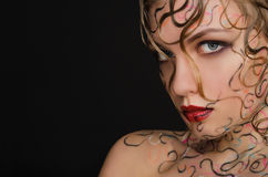 Woman with wet hair and face art. On black background Stock Photos
