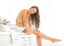 Woman with wet hair sitting in bathroom Stock Images