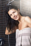Woman with wet hair standing in a shower Stock Photos