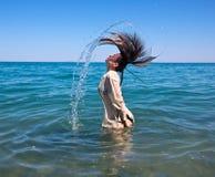 Woman  wet  hear splashing sea Royalty Free Stock Photography