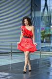 Woman in wet red dress at square Stock Image