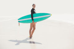 Woman in wetsuit holding a surfboard on the beach Stock Photos