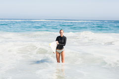 Woman in wetsuit holding a surfboard on the beach Royalty Free Stock Photos