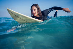 Woman in wetsuit with a surfboard on a sunny day Stock Images