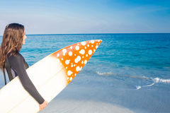 Woman in wetsuit with a surfboard on a sunny day Stock Photography