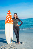 Woman in wetsuit with a surfboard on a sunny day Royalty Free Stock Image