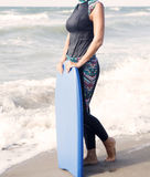 Woman in wetsuit and swimming board standing by the ocean Stock Photos