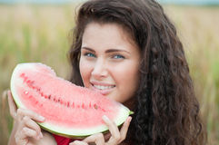 Woman in wheat field eating watermelon. Picnic. Royalty Free Stock Images