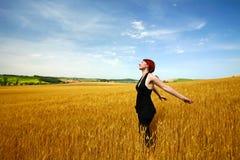 Woman in wheat field enjoying Stock Photos