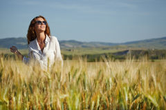Woman in wheat field enjoying, Stock Photo