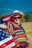 Woman in a wheat field with a USA flag royalty free stock photos