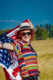 Woman in a wheat field with a USA flag royalty free stock images