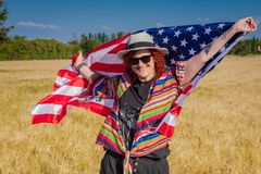 Woman in a wheat field with a USA flag stock images