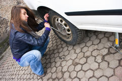 Woman during the wheel changing Royalty Free Stock Image