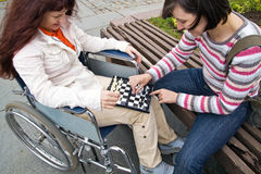 Woman in wheelchair. Plays with girlfriend in a chess Stock Photography