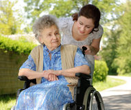 Woman in a wheelchair. Disabled senior woman in a wheelchair with her nurse Royalty Free Stock Image