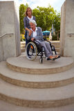 Woman in wheelchair is afraid. Elderly woman in wheelchair looking at inaccessible staircase Royalty Free Stock Image