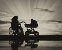 Woman in wheelchair and baby stroller near water and reflection Stock Photo