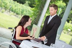 Woman on wheelchair calls up waiter in restaurant. Woman on wheelchair calls up the waiter in the restaurant Royalty Free Stock Photo
