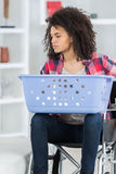 Woman on wheelchair carring basket to do laundry Royalty Free Stock Image