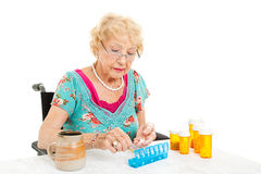 Woman In Wheelchair Counts Pills. Senior women in a wheelchair, couting out her pills for the week.  White background Stock Photo