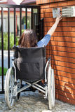 Woman on wheelchair dialing intercom Stock Images