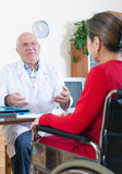 Woman in   wheelchair with    doctor. Stock Image