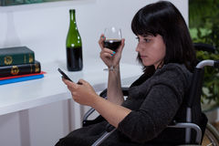 Woman on wheelchair drinking wine Stock Photography