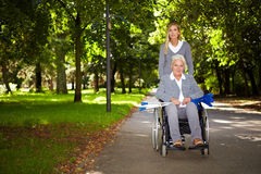 Woman in wheelchair driving in park. Happy woman in wheelchair with nurse in nature Stock Photography