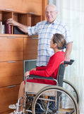 Woman in   wheelchair and   elderly man Royalty Free Stock Images