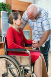 Woman in   wheelchair and   elderly man Royalty Free Stock Image